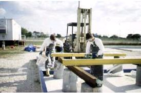 Workers applying PCRS to I-beams.