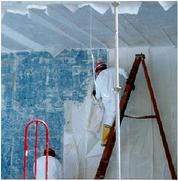 Worker removing laminated paper from a wall.