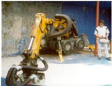 The SH-U11 concrete scabbler mounted on a Brokk 250 removing coating from a concrete floor.
